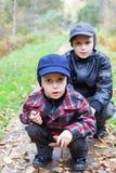 I ragazzi due dei fratelli si siedono la foresta della strada Immagini Stock