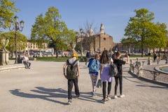 I ragazzi e le ragazze che indossano i loro zainhi stanno muovendo intorno il quadrato di Valle di della di Prato a Padova fotografie stock libere da diritti