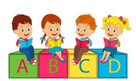 I ragazzi e le ragazze si siedono sui cubi e leggono il libro Immagini Stock