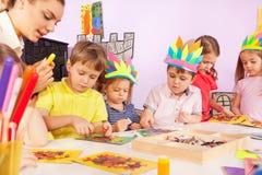 I ragazzi, le ragazze e l'insegnante incollano la carta a cartone Immagine Stock Libera da Diritti