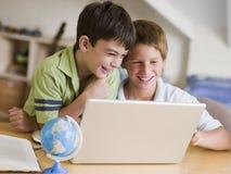 i ragazzi si dirigono i giovani usando del computer portatile due Fotografia Stock Libera da Diritti