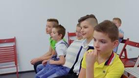 I ragazzi si siede alle sedie nella stanza archivi video