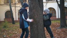I ragazzi stanno giocando il nascondino nel parco di autunno - movimento lento video d archivio