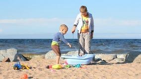 I ragazzi stanno giocando sulla spiaggia stock footage