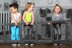 I ragazzini e la ragazza portano insieme le scale di legno Immagine Stock Libera da Diritti