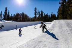 I ragazzini sciano/snowboard il mini mezzo tubo a Mammoth Mountain, la California U.S.A. Immagine Stock