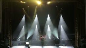 I raggi bianchi alternatamente infiammano in scena nello scuro Fase vuota di concerto archivi video