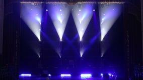 I raggi bianchi alternatamente infiammano in scena nello scuro Fase vuota di concerto stock footage