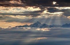 I raggi d'ardore del sole illuminano Julian Alps ed il mare nevosi delle nuvole Immagini Stock Libere da Diritti