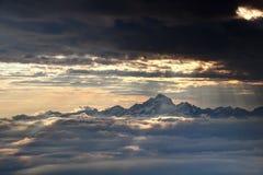 I raggi d'ardore del sole illuminano Julian Alps ed il mare nevosi delle nuvole Fotografia Stock