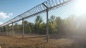I raggi del sole e gli alberi di autunno sono diretto visibile il recinto della prigione del metallo con filo spinato video d archivio