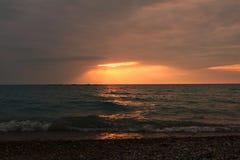 I raggi del sole irradiano attraverso le nuvole sull'acqua alla spiaggia della stazione in Kincardine, Ontario immagini stock