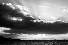 I raggi di Sun che escono con alcuno si rannuvola un lago Fotografia Stock