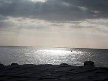 I raggi di Sun da parte a parte si rannuvola il mare Immagine Stock