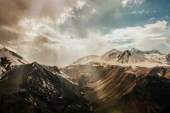 I raggi espongono al sole si fano strada attraverso la montagna nevosa delle nuvole Fotografie Stock