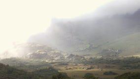 I raggi luminosi perforano le nuvole e la nebbia ed il lustro sulle rocce in una valle archivi video