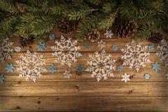 I rami ed i fiocchi di neve dell'albero di Natale ornano sulla tavola di legno naturale nel fondo fotografie stock