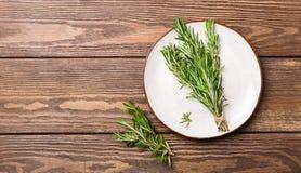 I ramoscelli dei rosmarini fragranti freschi sono raccolti in un panino che si trova su un piatto bianco su un fondo di legno Cop immagini stock libere da diritti