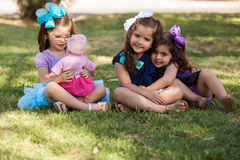 I rather play with my doll. Beautiful little girl playing with her doll while ignoring her friends at a park Royalty Free Stock Images