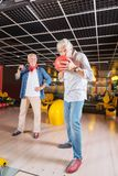 Pleasant aged man playing bowling together at day stock photo