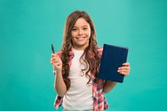 I am ready for school. Child smart kid hold pen and notepad. Girl cute happy face likes to study blue background. Child. Girl holds book and pen. Back to school royalty free stock photo