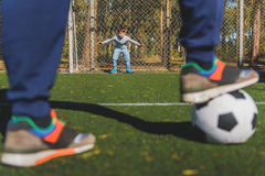 I am ready to catch this ball. Father and son are playing football on field. Boy is standing at gate and waiting for pass royalty free stock photo
