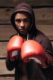 I am ready to fight. Confident young African man in hooded shirt and boxing gloves looking at camera while standing against wooden background Royalty Free Stock Images