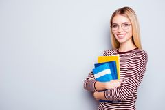 I am ready to start applying for university! Cute clever confide. Nt beautiful young woman wearing striped sweater and round glasses is holding a pile of book in Stock Photos