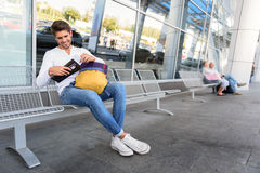 I am ready for trip. Joyful young man is sitting on chair near airport outdoors and reading ticket. He is laughing Stock Photography