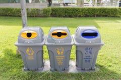 I recipienti in parco per la bottiglia di vetro possono, bottiglia di plastica, sacco di carta altro rifiuti alimentari dello spr Immagini Stock Libere da Diritti