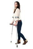 I am recovering slowly. Full length image of teen walking with crutches Stock Photos