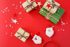 I regali di Natale hanno imballato nella carta kraft su un fondo rosso immagine stock