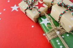 I regali di Natale hanno imballato nella carta kraft su un fondo rosso immagini stock libere da diritti