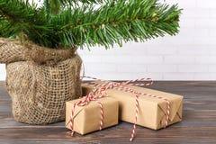 I regali differenti del ` s del nuovo anno avvolti in carta da imballaggio sotto l'albero di Natale si ramificano immagine stock