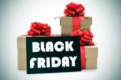 I regali e un'insegna con il testo anneriscono venerdì Immagini Stock