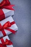 I regali inscatolati con gli archi rossi legati su grey sorgono il concetto di feste Fotografie Stock