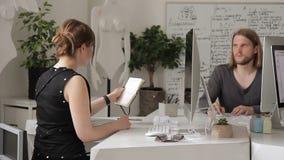 I regeringsställning visar kvinnan en man en anteckningsbok med anmärkningar på hennes skrivbord lager videofilmer