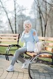 Alert woman drinking coffee while sitting on the bench. I am relaxing. Happy blond woman drinking coffee while sitting on the bench royalty free stock images