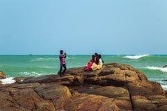 I residenti locali guardano il tramonto fuori dalla costa di Kanyakumari Immagine Stock