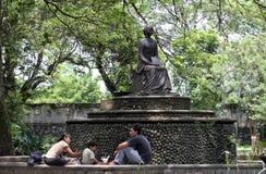 I residenti si rilassano nel parco sotto una statua Partini Balaikambang Immagini Stock