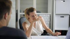 I responsabili di ufficio ridono felicemente insieme tutti durante il giorno lavorativo stock footage