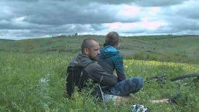 I resti amorosi di una coppia dopo una bici guidano nel parco su un giacimento di fiore Un bello giovane con una donna sta sedend stock footage