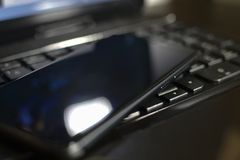 I resti del telefono sulla tastiera del computer portatile Fotografia Stock Libera da Diritti