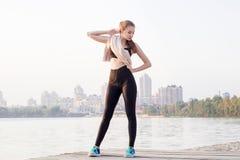 I resti sportivi della donna di forma fisica abbastanza esile dei giovani e si pulisce w Fotografia Stock