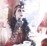 I retro anni 20 della donna - gli anni 30 che si siedono in un ristorante Fotografie Stock