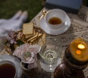 I retro stil på en tetabell en kaka i en korg per exponeringsglas och blommor Royaltyfria Bilder