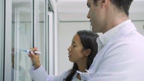 I ricercatori di ricerca medica scrive la formula scientifica su una lavagna di vetro video d archivio