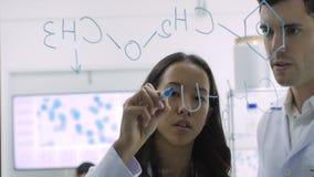 I ricercatori di ricerca medica scrive la formula scientifica su una lavagna di vetro stock footage