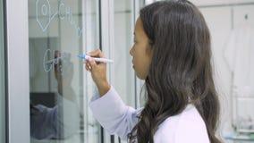 I ricercatori di ricerca medica scrive la formula scientifica su una lavagna di vetro archivi video
