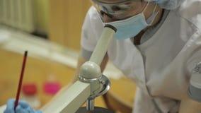 I ricercatori medici femminili che lavorano con i microscopi e le provette in laboratorio condiziona, studia e prende stock footage